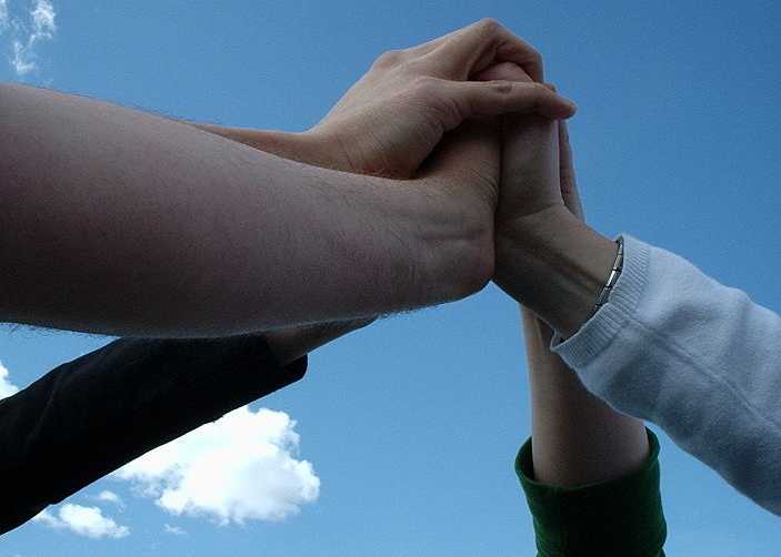 picture of four hands clasped together
